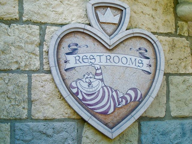 The Chesire Cat points this way to a uniquely themed set of restrooms at Disneyland tied to Alice in Wonderland. Here stall doors are like playing cards. Photo by J. Jeff Kober.