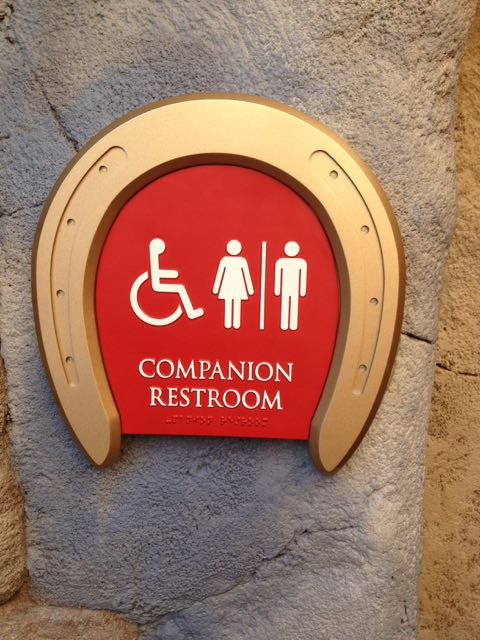 "At Disneyland, a ""golden"" horseshoe meant a restaurant. Here it's an invitation to a companion restroom in Fantasyland at the Magic Kingdom. Companion restrooms are a major addition to Disney parks over the last dozen years. Also note the braille on the sign. Photo by J. Jeff Kober."