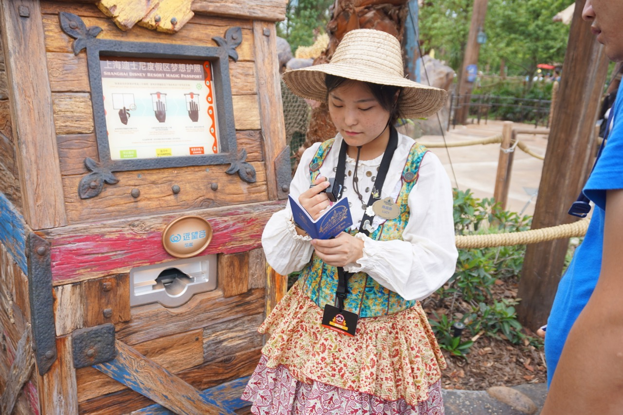 A Cast Member focuses on in interactive passport for guests exploring the park. Photo by J. Jeff Kober.